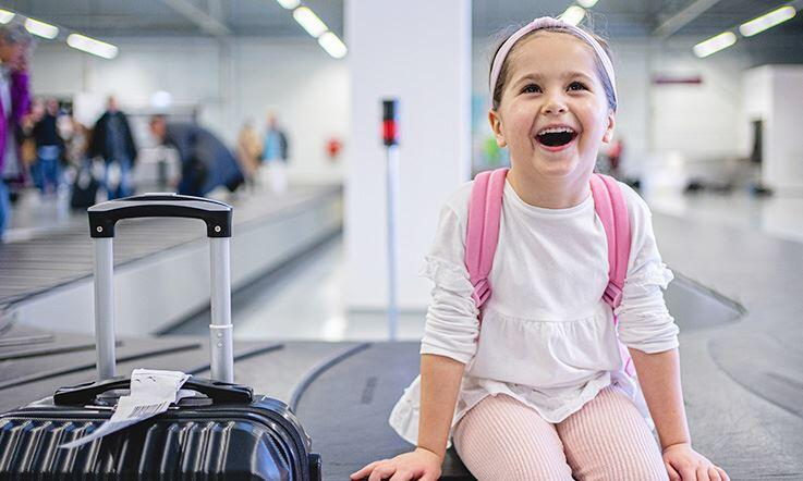 A smiling child, with a hold suitcase next to her, sits at the foot of the baggage collection treadmill, inside an airport. The room is lit up, and in the background there are several people collecting their belongings.