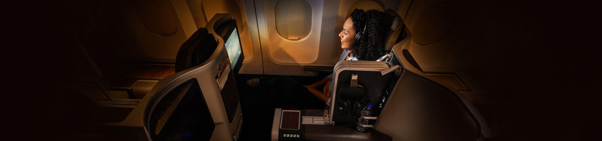 Smiling passenger, in Executive Class, sitting in a large, spacious and more comfortable chair, in a calm and dark environment, without people around it. You are watching some kind of entertainment on board, on the chair screen, with the TAP headphones put on.